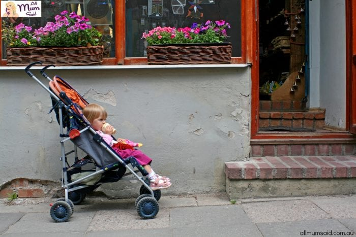 child sitting in the pram in front of the shop doors, eating ice cream and waiting for parent