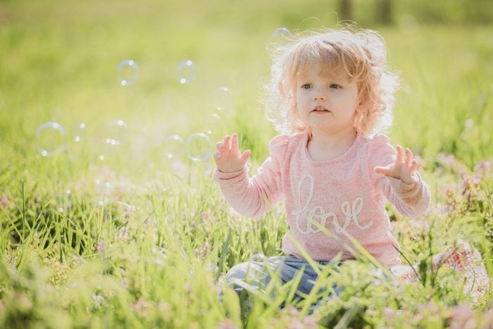 toddler playing with bubbles in nature