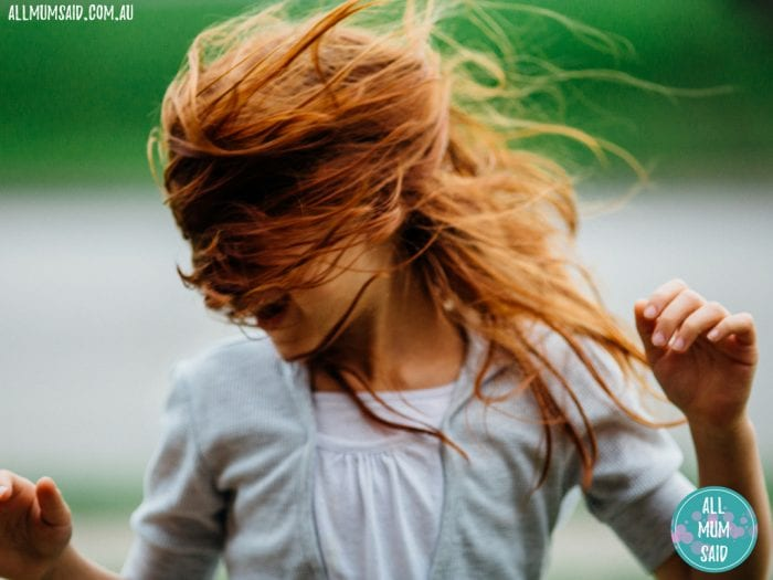 Young girl with red hair happy dancing child