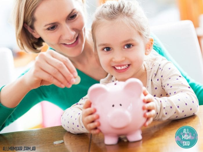 Mother and daughter putting coins into piggy bank | teach kids the value of money - toddler, primary and teens