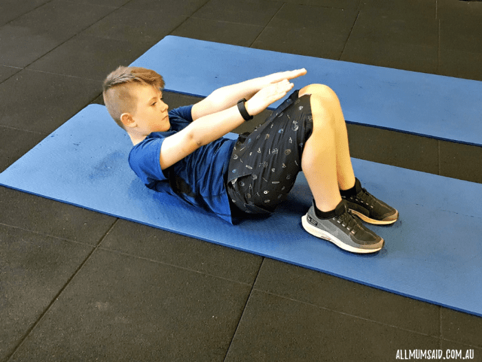 Child doing crunches exercise keeping active wearing Laser V-Fitness activity tracker