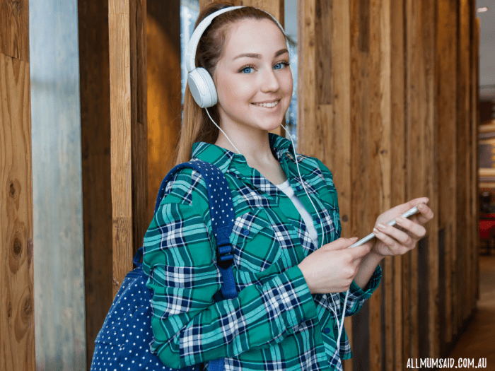 teen wearing headphones and using phone at school - school friendly tech