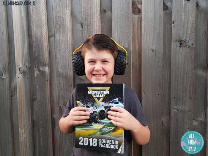 Boy with Monster Jam book and earmuffs