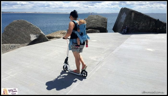 Globber 18.0 by Kleefer | woman babywearing while riding adult scooter at Newcastle breakwall