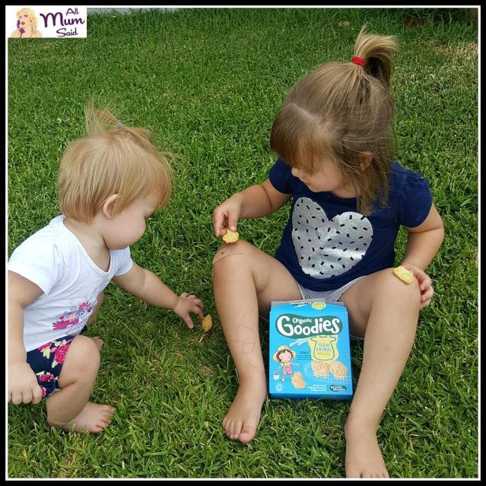 Girls sitting down eating organix goodies farm biscuits | healthy toddler snacks