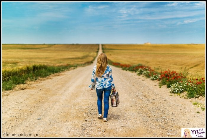 Packed suitcase woman walking down dirt road going on holidays