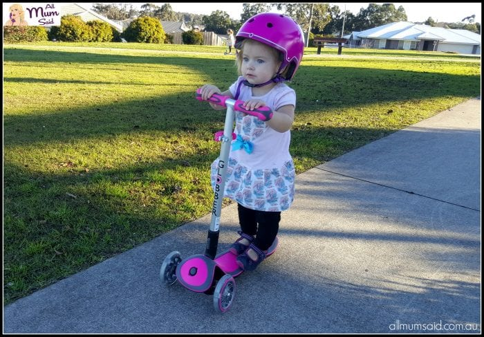 Toddler riding globber scooter and wearing globber helmet at park