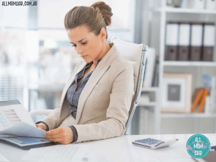 beautiful woman working in office at computer with files