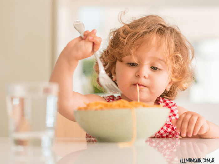 toddler eating spaghetti from a bowl