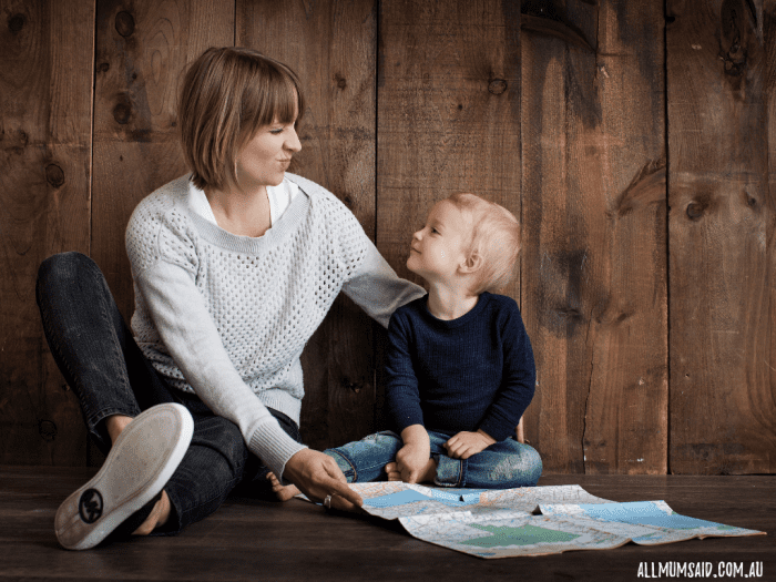 mum and son looking at each other with a map sitting on the floor