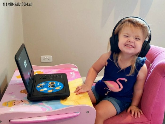 Toddler watching portable DVD player with bluetooth headphones