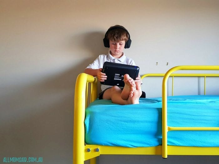 kid watching portable DVD player with bluetooth headphones