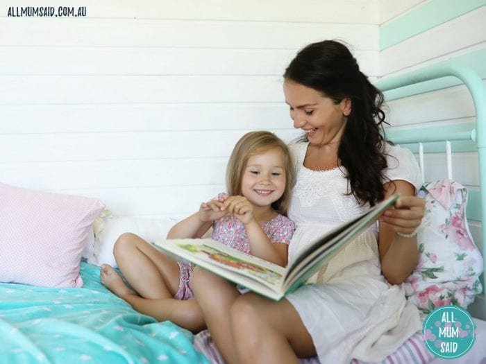 Mum reading book to child on bed