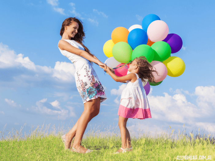 well-dressed mum playing in park with daughter holding balloons parenting styles - perfect mum