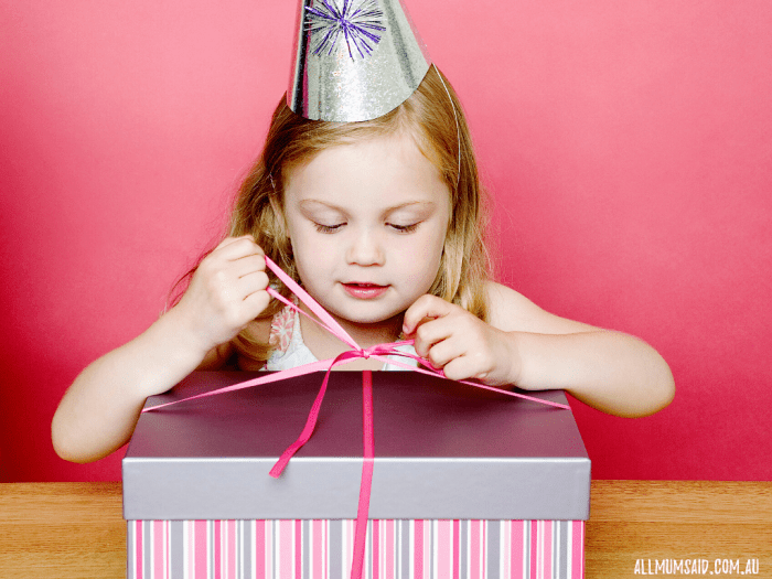 girl opening present - gifts that aren't toys